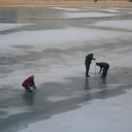 Men Drilling a Hole to Fish on Tianjin's Frozen River, China
